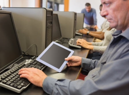 Man in computer class looking at tablet pc in college photo