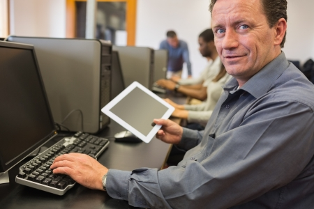 Mature student holding tablet pc in computer class Stock Photo - 15584431