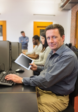 Mature student in computer class holding tablet pc in college photo