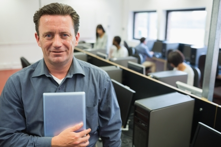 50s adult: Man holding a tablet pc in computer room and smiling