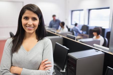 profesor alumno: Mujer sonriendo y de pie en la parte delantera de la clase de computaci�n Foto de archivo