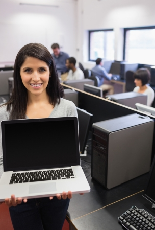 Woman presenting a laptop in the computer class photo