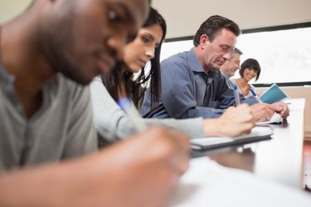 salon de clases: Los estudiantes en una conferencia con una mujer mirando hacia arriba en la universidad