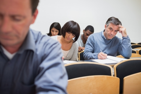 Man looking up from taking notes in class photo