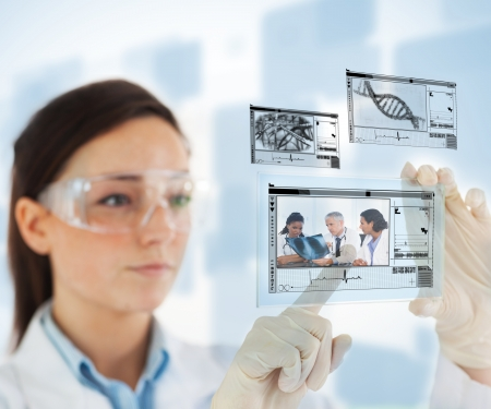 nurse gloves: Woman selecting medical images from hologram interface on blue background Stock Photo