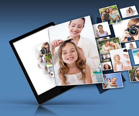 Tablet computer showing many family images on blue background photo
