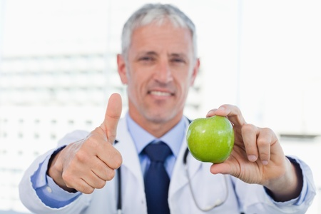 Doctor showing an apple with the thumb up in his office photo