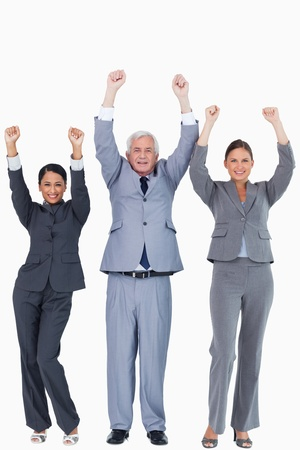 Three businesspeople with arms up against a white background photo