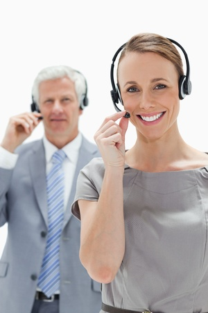 Smiling woman wearing a headset with a  man in background photo