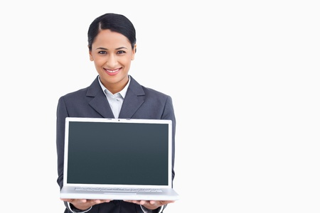 Close up of smiling saleswoman presenting laptop screen against a white background photo