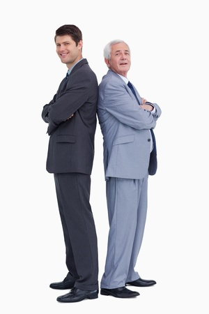 Smiling businessmen standing back to back against a white background Stock Photo - 18679289