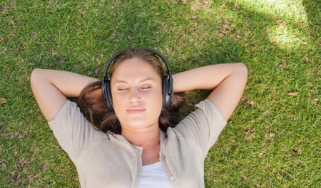 Relaxed young woman listening to music while lying on the lawn photo