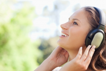 Side view of a young woman in the park listening to music photo