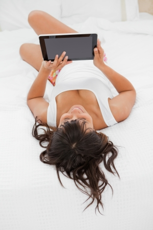 Rear view of a smiling young woman using a touch pad on her bed photo