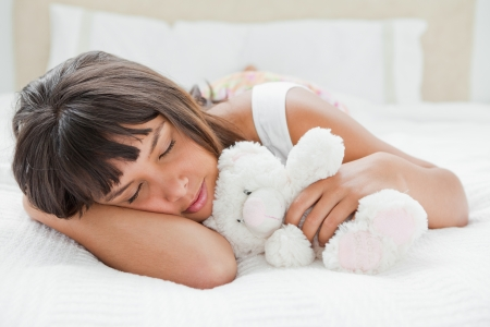 Young woman sleeping with a teddy bear on her bed photo
