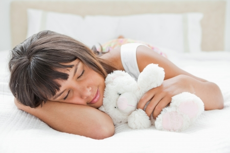 Cute young woman sleeping with a teddy bear on her bed photo