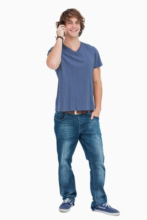 Happy male student on the phone against white background photo
