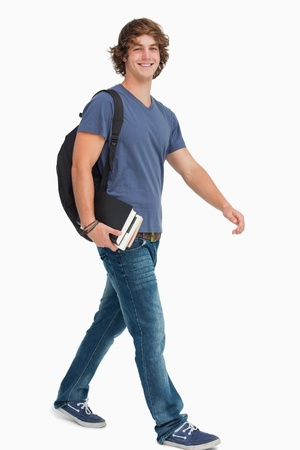 person walking: Male student with a backpack holding books while walking against white background Stock Photo