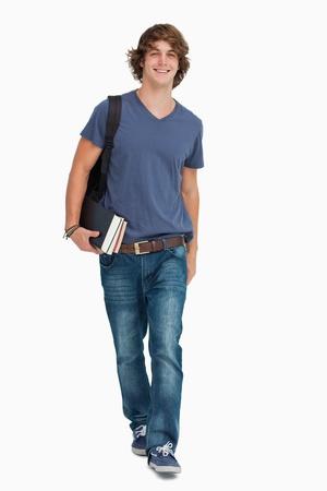 Vooraanzicht van een mannelijke student wandelen met een rugzak en boeken tegen een witte achtergrond