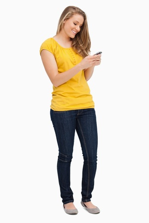 Attractive blonde woman smiling while using her cellphone against white background photo