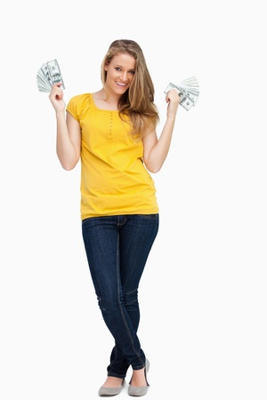 crossed legs: Beautiful blonde woman smiling with a lot of dollars against white background Stock Photo