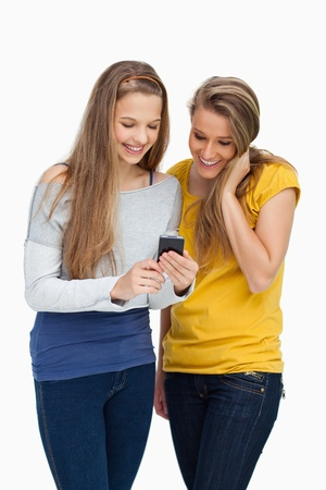 Two females student smiling while looking a cellphone against white background photo