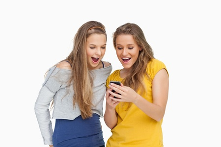 voiceless: Two voiceless young women looking a smartphone against white background