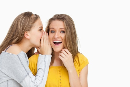voiceless: Blonde student whispering to a friend against white background Stock Photo