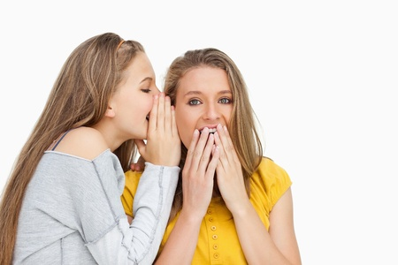 voiceless: Blonde student whispering to her voiceless friend against white background Stock Photo