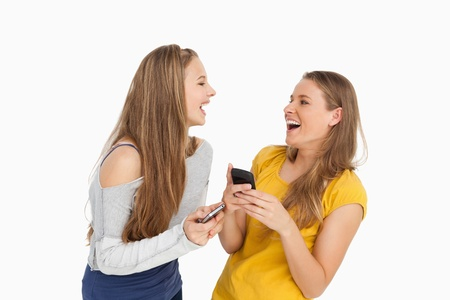Two young women laughing while holding their cellphones against white background photo