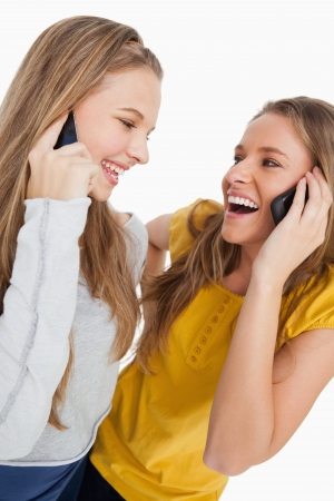 Close-up of two beautiful students laughing on the phone against white background photo