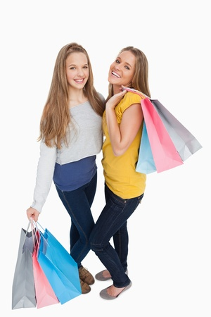 Two beautiful young women holding shopping bags against white background Stock Photo - 16051542