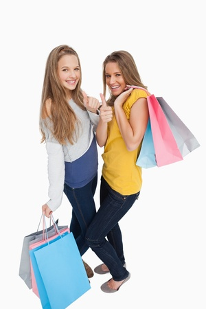 thumbup: Two beautiful young women with shopping bags the thumb-up against white background