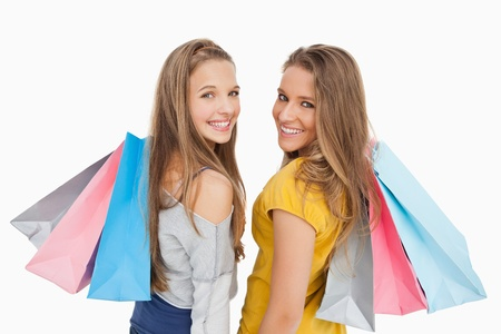 Two young women with shopping bags against white background Stock Photo - 16052919