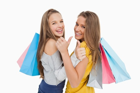 Rear view of two young women the thumb-up with shopping bags against white background Stock Photo - 16051825