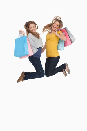 Two young women jumping with shopping bags against white background Stock Photo - 16049641