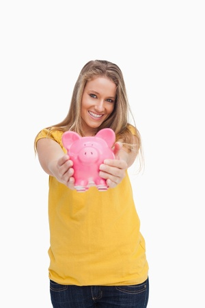 tending: Young blond woman tending a piggy-bank against white background Stock Photo