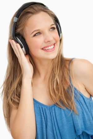 Close-up of a beautiful young woman wearing headphones against white background photo