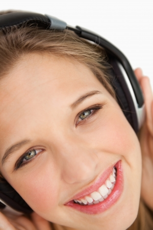 greeneyes: Close-up of a green-eyes woman listening to music against white background Stock Photo