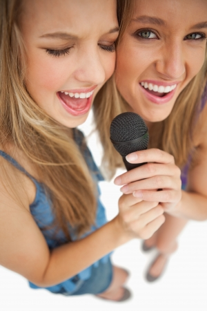 greeneyes: High-angle shot of two happy young blonde singing against white background