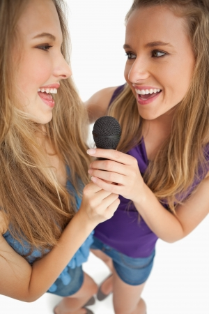 greeneyes: High-angle shot of two happy young beauty singing together against white background