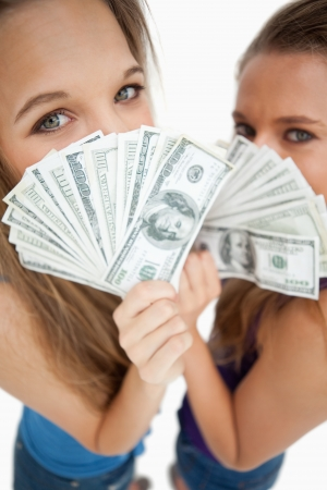 greeneyes: High-angle view of two young woman behind dollars against white background