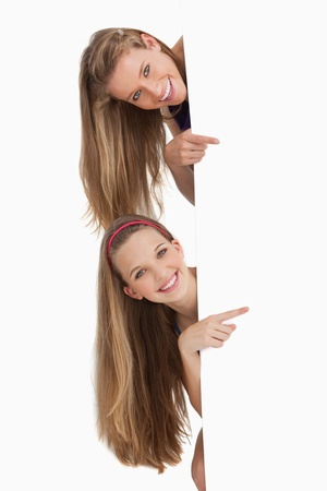 Portrait of two long hair students pointing behind a blank sign against white background photo