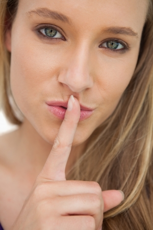 greeneyes: Green-eyes young woman with a finger on the lips against white background