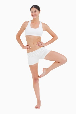 legs crossed at knee: Slim woman with a yoga position against white background Stock Photo