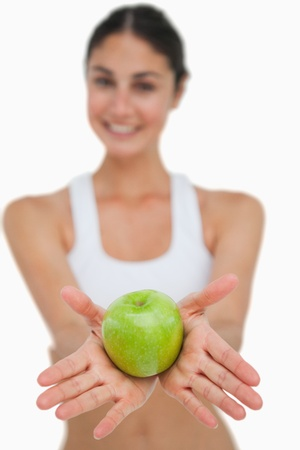 Close-up a green apple holding by a brunette against white background photo