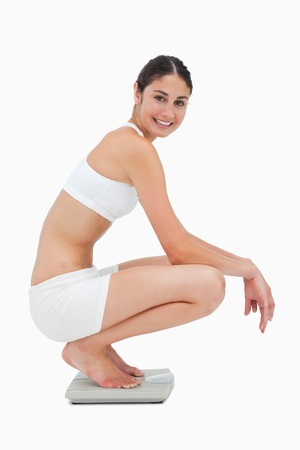 bathroom scale: Slim young woman smiling while sitting on a scales against white background