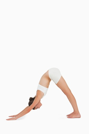 downward: Woman doing yoga against white background
