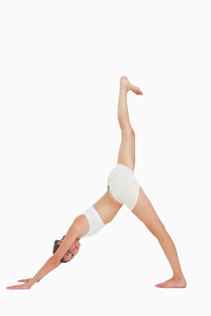 Woman doing yoga while looking at camera against white background photo