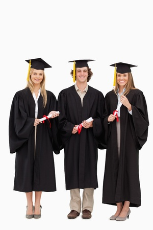 Three students in graduate robe holding a diploma against white background photo